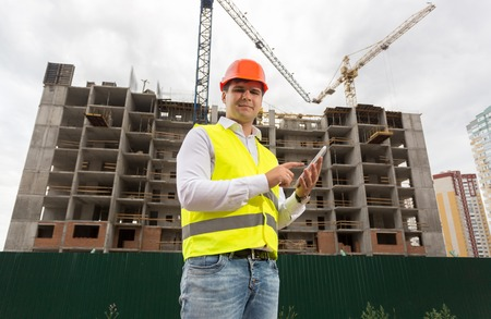 Portrait of smiling male architect using digital tablet on building site