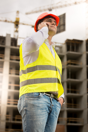 Young construciton engineer in hardhat talking by phone against building under construction