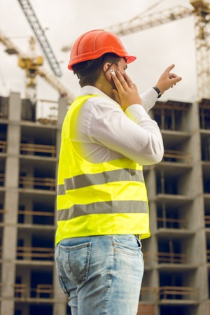 Toned photo of man in safety vest and protective hardhat talking by phone and pointing at building under construction. Concept of investing in real estate