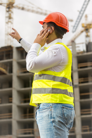 Young businessman talking by phone and pointing at building site. Concept of investing in real estate