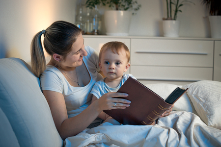 Happy smiling mother reading stories to her baby son at night Stock Photo