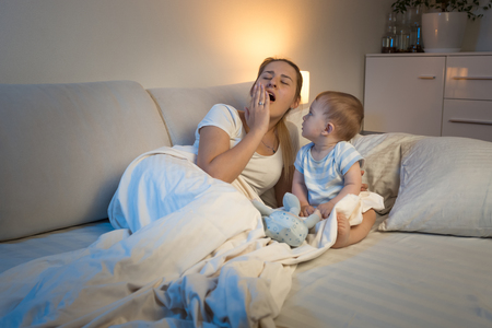 Cute baby boy sitting in bed and looking his tired yawning mother Stock Photo