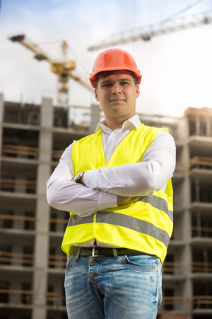 Portrait of smiling businessman in hardhat and safety vest posing against building under construction