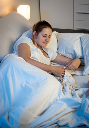 Young woman lying in bed at night and using digital tablet Stock Photo