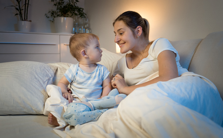Portrait of smiling young mother and baby boy lying in bed at night and looking at each other Stock Photo