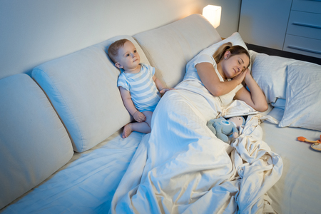 9 motnhs old sleepless baby sitting on bed next to sleeping young mother