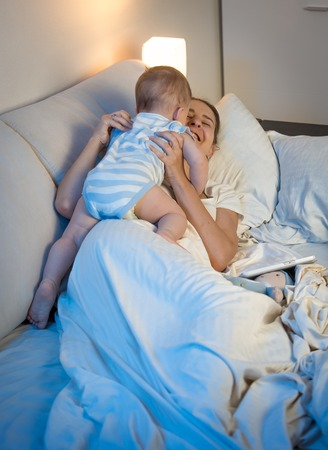 Portrait of laughing young woman having fun with her baby boy in bed before going to sleep Stock Photo