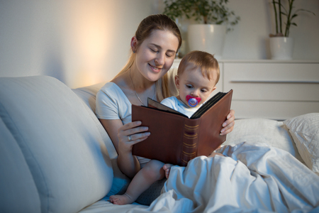 Beautiful smiling woman reading big old book to her baby boy before going to sleep