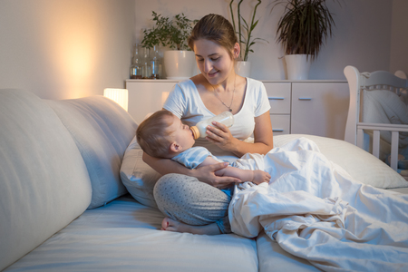 Portrait of young woman in pajamas feeding her baby son at night