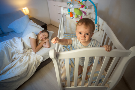 Cute sleepless smiling baby boy standing in cot next to sleeping young mother Stock Photo