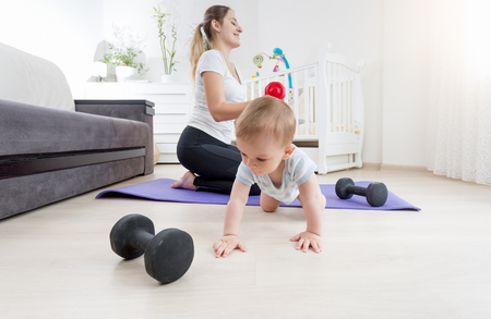 Adorable baby boy crawling on floor while his mother practicing fitness at home Stock Photo