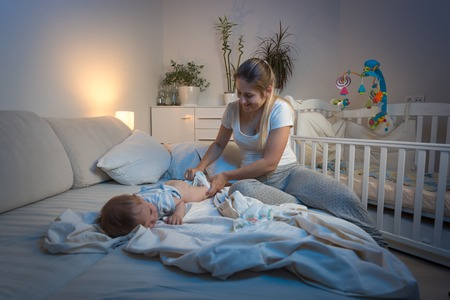 Beautiful young mother changing diapers to her baby boy at night Foto de archivo