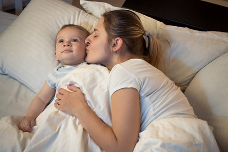 Portrait of loving young mother kissing her baby son before going to sleep Stock Photo