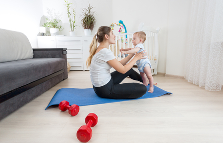 Beautiful young woman doing fitness exercises with her baby boy on floor at home