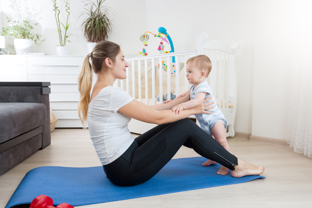 Cute baby boy exercising with young mother on fitness mat at home
