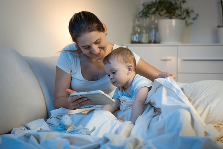 Young smiling with baby boy watching cartoons on digital tablet before going to sleep