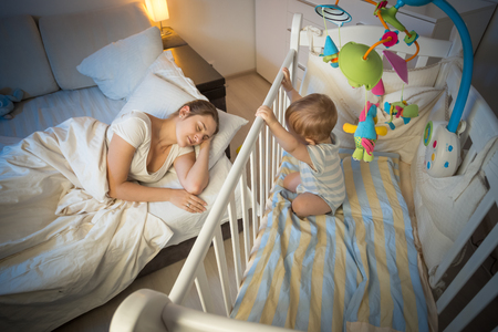 Sleepless 9 months old baby boy looking at tired mother sleeping in bed Stock Photo