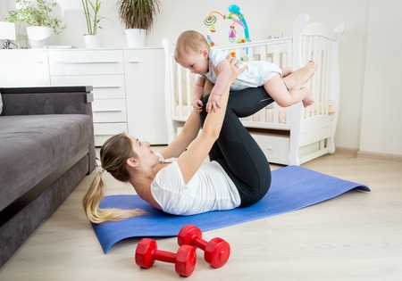 Young smiling woman in leggings exercising on floor at home with her cute baby boy