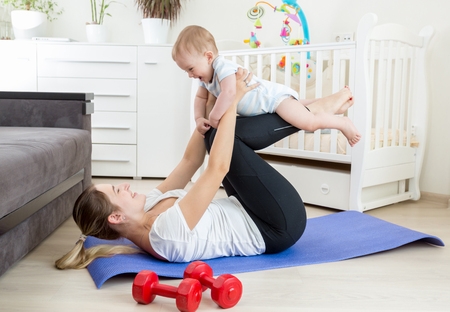 Happy laughing baby boy exercising with mother on yoga mat at home