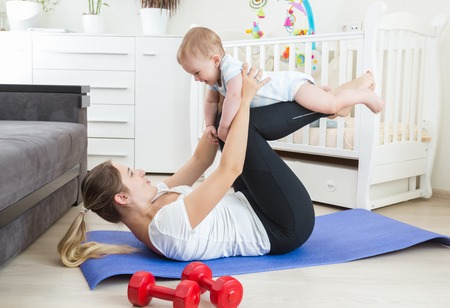 Beautiful smiling baby boy practising fitness with young mother on floor at home