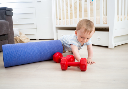 Cute baby boy playing with fitness equipment on floor at home