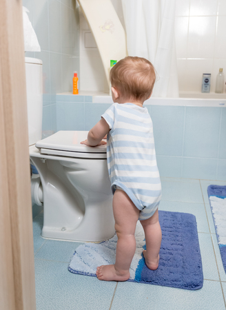 Cute 9 months old baby boy standing at toilet Stock Photo