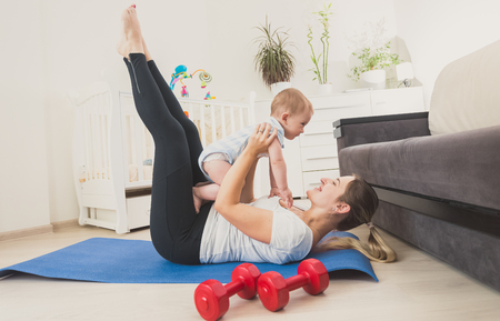 Beautiful young woman holding her baby boy and exercising on floor at home