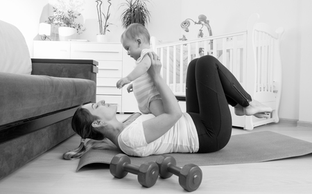 Black and white image of young woman exercising with her 9 months old baby son at home
