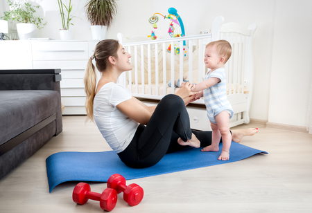 Cute 9 months old baby boy exercising with young mother on fitness mat at home