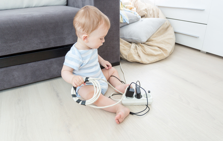 Unatteded little baby boy playing with electric power cables. Child in dangerous situation Stock Photo