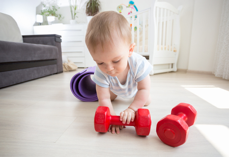 Portrait of cute baby boy palying with red dumbbells on floor at home