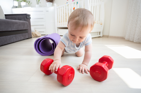 Cute 9 months old baby boy holding big red dumbbells. COncept of children in sport