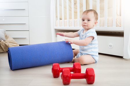 Portrait of adorable 9 months old baby boy playing with dumbbells and fitness mat at home