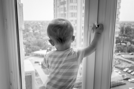 Black and white image of baby pulling window handle and trying to open it