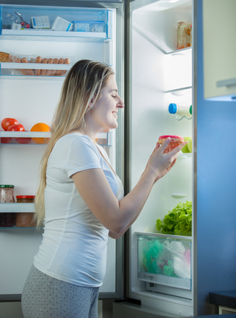 Smiling hungry woman taking sweet donut out of refrigerator at night