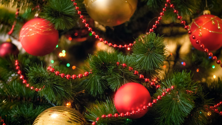 Closeup photo of Christmas tree branches with hanging colorful baubles