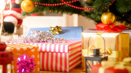 Closeup image of colorful Christmas gift boxes lying under Christmas tree at morning