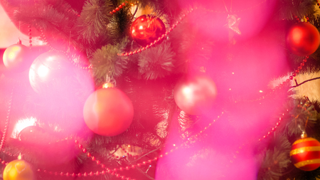 Beautiful abstract image of pink sparkling lights shining over decorated Christmas tree