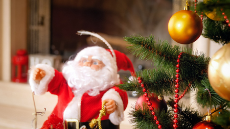 Closeup image of Santa Claus figure and Christmas tree at living room Stock Photo
