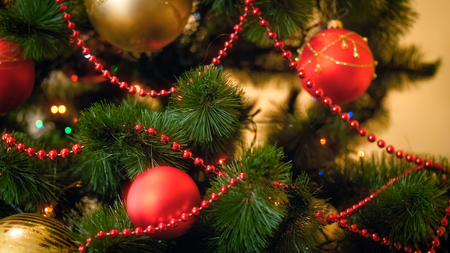 Closeup photo of red and golden baubles adorning Christmas tree