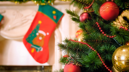 Closeup image of adorned Christmas tree against decorated mantelpiece with hanging stockings for gifts