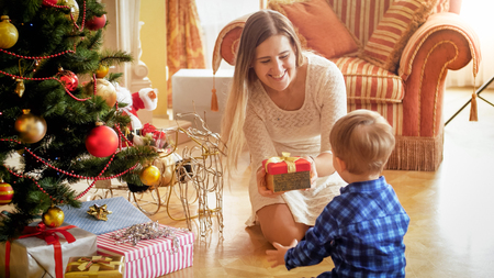 Happy smiling mother giving Christmas gift to her toddler son