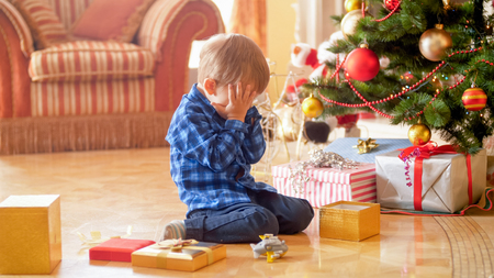 Little toddler boy sitting under Christmas tree and crying