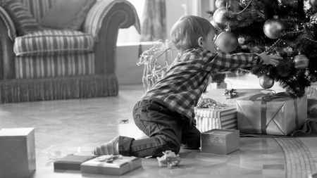 Black and white image of little boy sitting on floor and reaching for gifts under Christmas tree