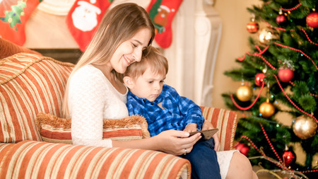 Happy smiling mother with her son watching video on smartphone on Christmas