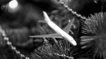 Black and white closeup image of toy airplane lying on Christmas tree branches. Concept of winter holidays travelling Stock Photo