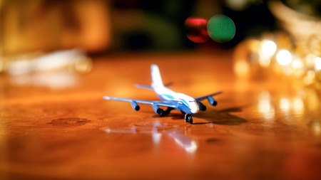 Closeup image of miniature toy airplane against glowing Christmas lights. Concept of winter holidays travelling
