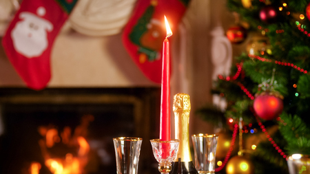 CLoseup image of burning festive candle against fireplace and decorated Christmas tree