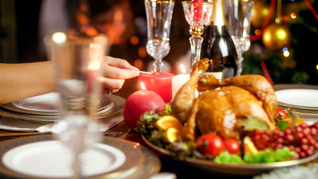 Closeup photo of lighting up candles on Christmas dinner table against burning fireplace Stock Photo
