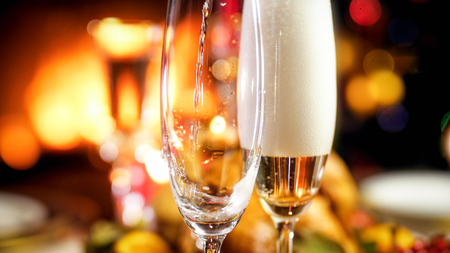 Closeup photo of champagne flowing in two glasses against burning fireplace